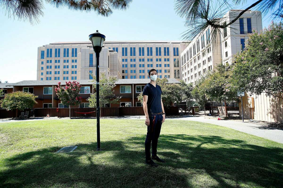 Portrait of Stanford University PHD graduate student Tyler Benster, who is photographed in front of his current housing the brown units and the new tower under construction. At Stanford University, California, on Friday, August 7, 2020.