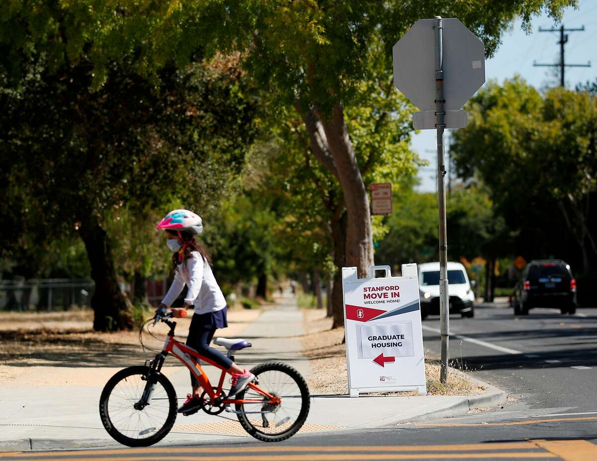 Bicyclist rides pass the Stanford graduate housing move-in sign on display near Stanford University, California, on Friday, August 7, 2020.