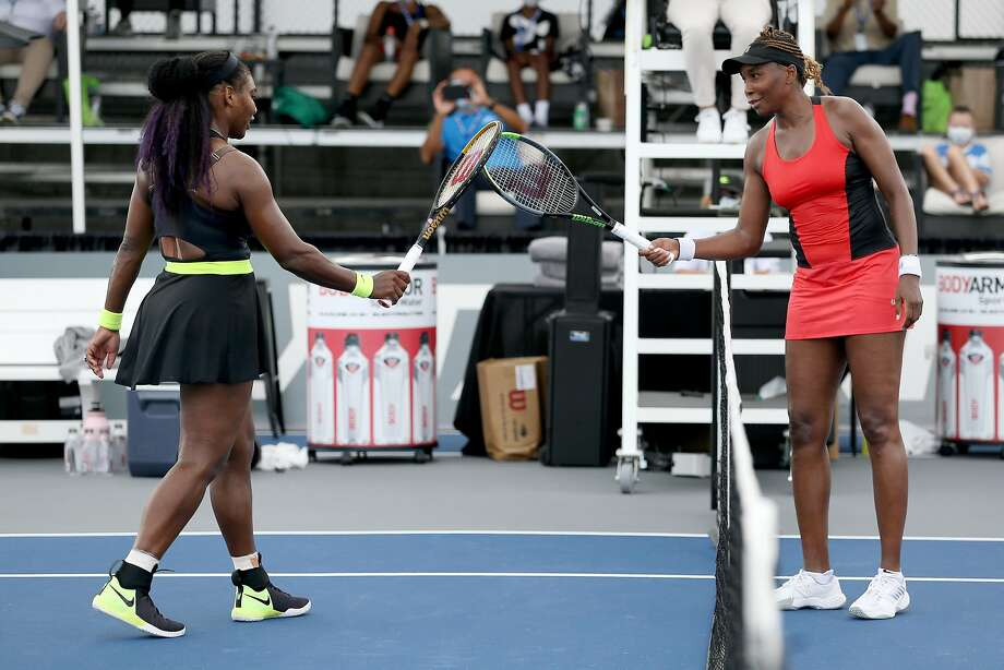 No hugs or hand-shaking thanks to the WTA's coronavirus protocol, so after Serena Williams (left) beat older sister Venus Williams 3-6, 6-3, 6-4, they touched rackets. Photo: Dylan Buell / Getty Images