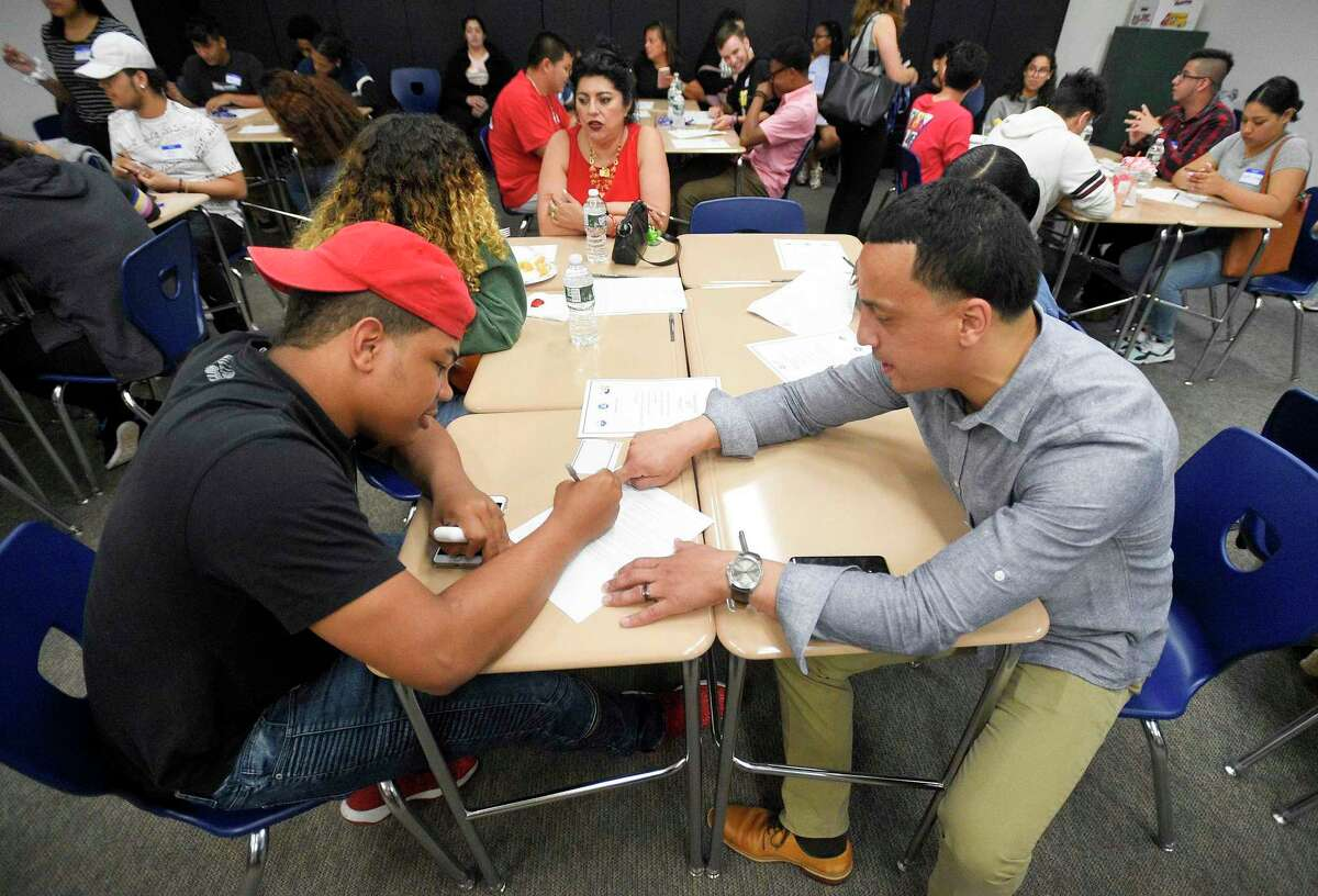 Thomas Agosto, dean of students for Stamford High School, helps Westhill High School graduate Robinson Reyes fill out college forms on June 20, 2019. Agosto's position was cut earlier this summer, but the Board of Education was able to bring it back on Tuesday.