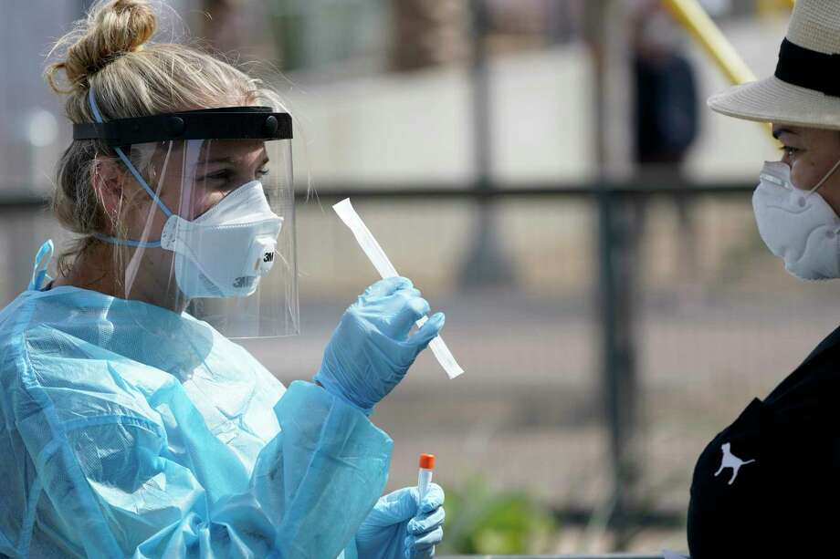 Nurse practitioner Debbi Hinderliter, left, collects a sample from a woman at a coronavirus testing site near the nation's busiest pedestrian border crossing, Thursday, Aug. 13, 2020, in San Diego. San Diego County has started operating a testing site next to the city's largest pedestrian link to Tijuana, Mexico. (AP Photo/Gregory Bull) / Copyright 2020 The Associated Press. All rights reserved