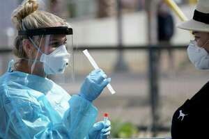 Nurse practitioner Debbi Hinderliter, left, collects a sample from a woman at a coronavirus testing site near the nation's busiest pedestrian border crossing, Thursday, Aug. 13, 2020, in San Diego. San Diego County has started operating a testing site next to the city's largest pedestrian link to Tijuana, Mexico. (AP Photo/Gregory Bull)