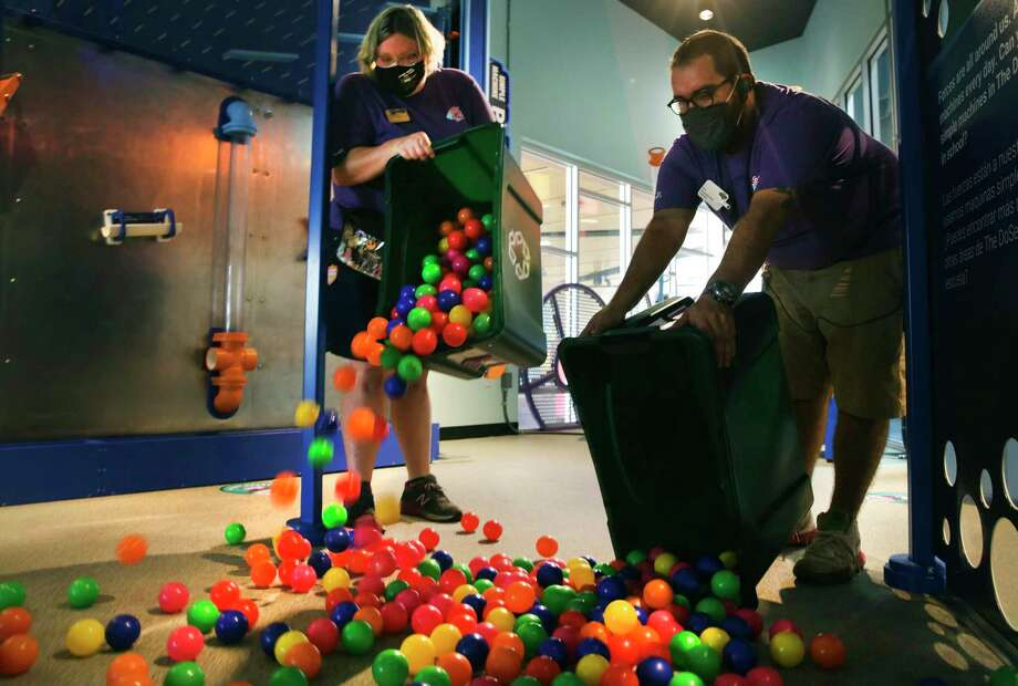 Kari Blalack (left) and Nick Perez pour cleaned plastic balls onto the DoSeum's Force Course. Photo: Bob Owen /Staff Photographer / ©2020 San Antonio Express-News