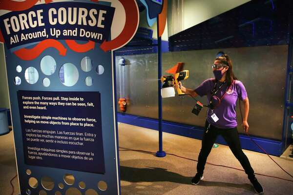 Jenevy Sepulveda sprays a disinfectant on a display at the DoSeum, which is cleaned three times a day.