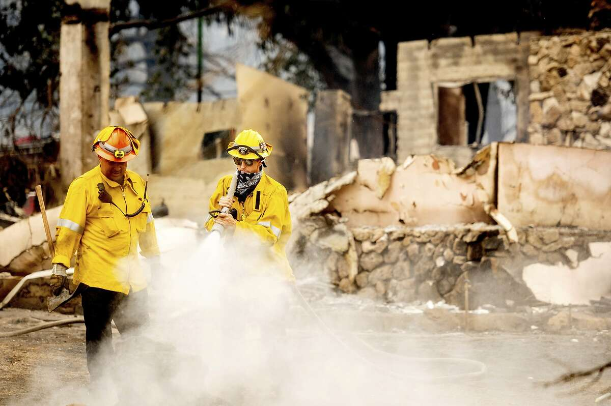 A Los Angeles County firefighter extinguishes hot spots at a scorched residence while battling the Lake Fire in the Angeles National Forest, Calif., north of Santa Clarita on Thursday, Aug. 13, 2020. Light winds and scattered thundershowers early Thursday helped calm the flames of a huge wildfire that prompted evacuations north of Los Angeles, and firefighters hoped to rein in the blaze before temperatures spike later in the day. (AP Photo/Noah Berger)