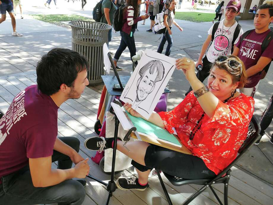 TAMIU student Agustin Gonzalez reacts as he sees a caricature of himself by Erica Missey Wednesday, August 29, 2018 at the TAMIU Campus. TAMIU is hosting events this week as part of the 2018 Welcome Week hosted by the Campus Activities Board and the Student Government Association. Photo: Cuate Santos / Laredo Morning Times