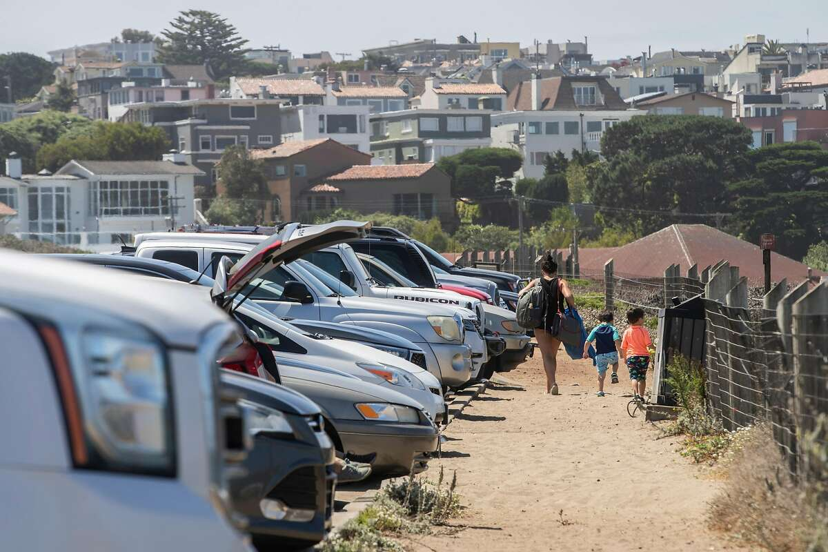 A person and children leave Baker Beach on Thursday, Aug. 13, 2020, in San Francisco, Calif. The parking lot is filled with cars, despite the closed Bowley Street, which leads to the access road to Baker Beach. People are driving past the road closure to reach the parking lot.
