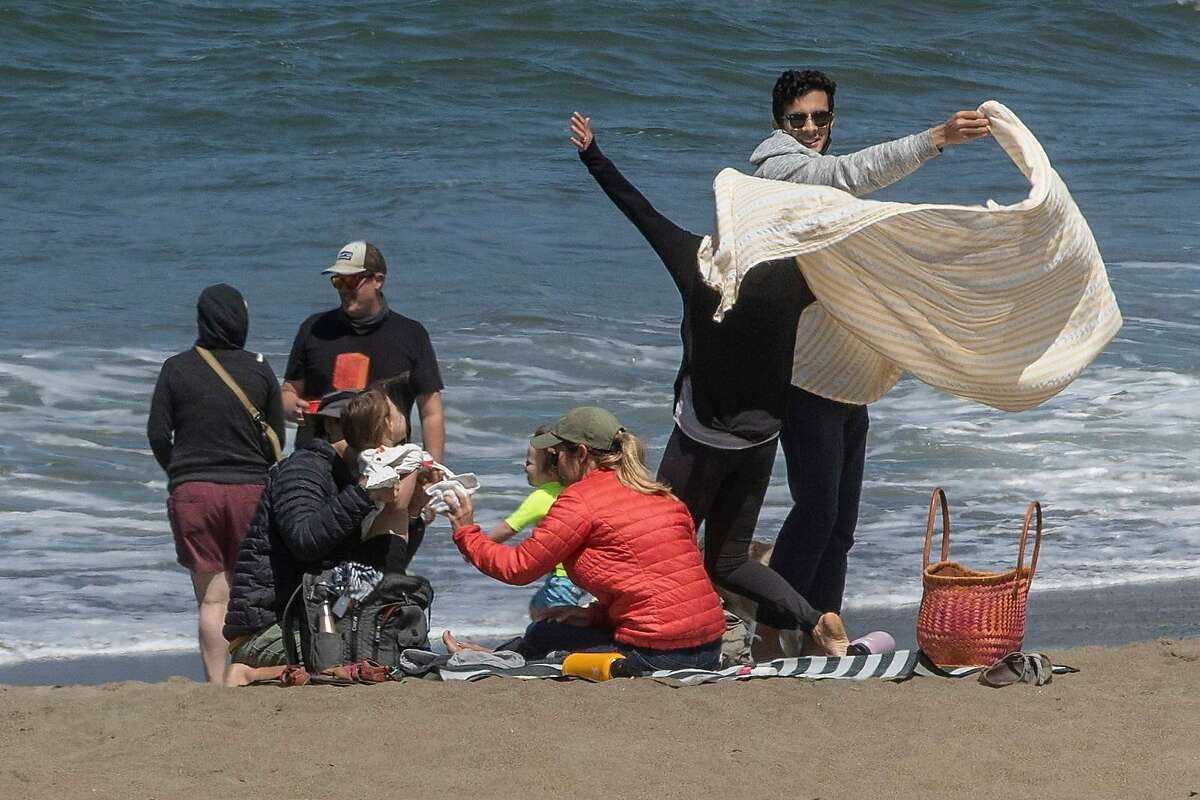 Beachgoers pack up their belongings at Baker Beach on Thursday, Aug. 13, 2020, in San Francisco, Calif.