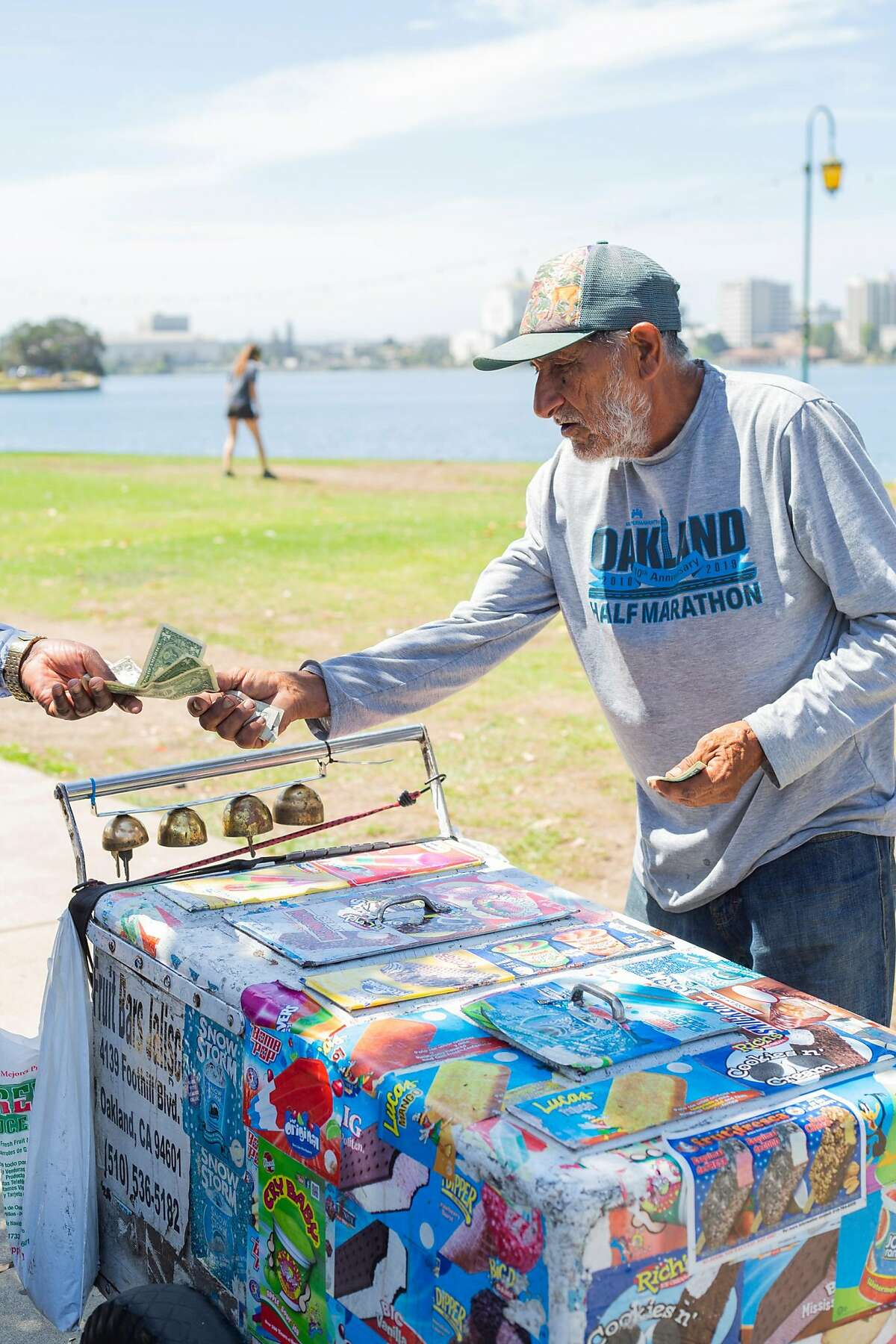 Juan, (lastname withheld) hands a customers his change on the edge of Lake Merrit on Thursday August 13, 2020 in Oakland, CA. Juan has been selling icecream by Lake Merrit for over 5 years.