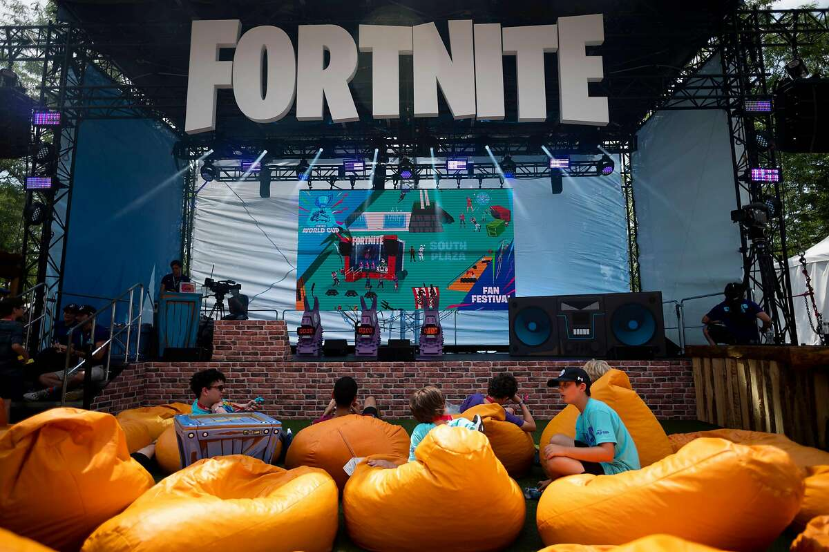"""(FILES) In this file photo boys sit on pillows outside during the 2019 Fortnite World Cup Finals - Round Two on July 27, 2019, at Arthur Ashe Stadium, in New York City. - The maker of video game sensation """"Fortnite"""" on August 13, 2020 sued Apple for the way it rules over the App Store, accusing the iPhone maker of wielding monopoly power. Epic Games called on a federal judge to order Apple to stop its """"anti-competitive conduct"""" and invalidate the tech giant's rules requiring app developers to pay 30 percent of transactions as the price of doing business in the App Store. (Photo by Johannes EISELE / AFP) (Photo by JOHANNES EISELE/AFP via Getty Images)"""