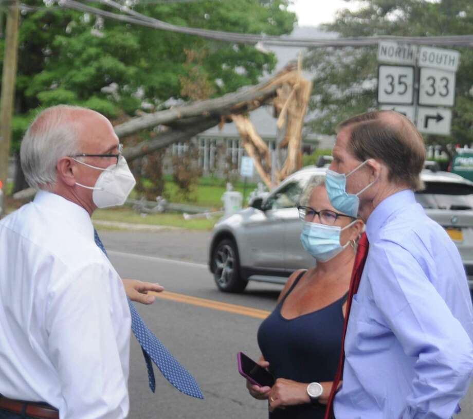 First Selectman Rudy Marconi, left, Bernard's owner Sarah Bouissou and U.S. Senator Richard Blumenthal discussed the lengthy storm clean-up Wednesday. The splintered tree which fell across Route 33 is visible behind them. Photo: Macklin Reid / Hearst Connecticut Media