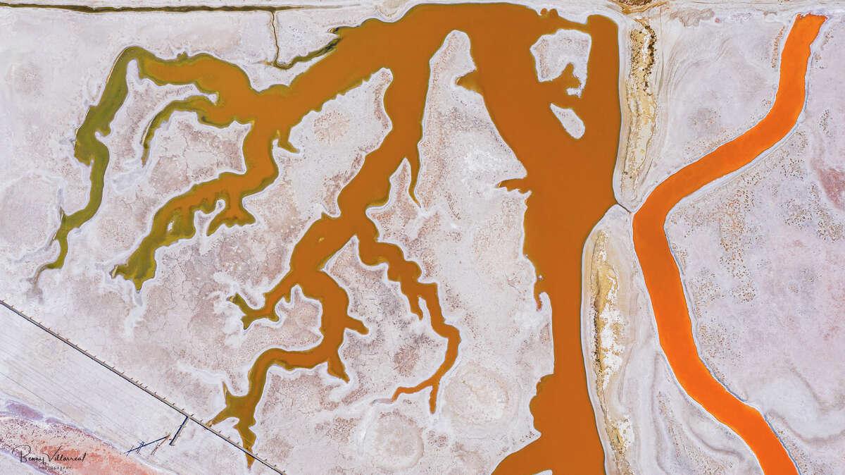 Rivers run an eerie shade of orange along an alkaline white shoreline.