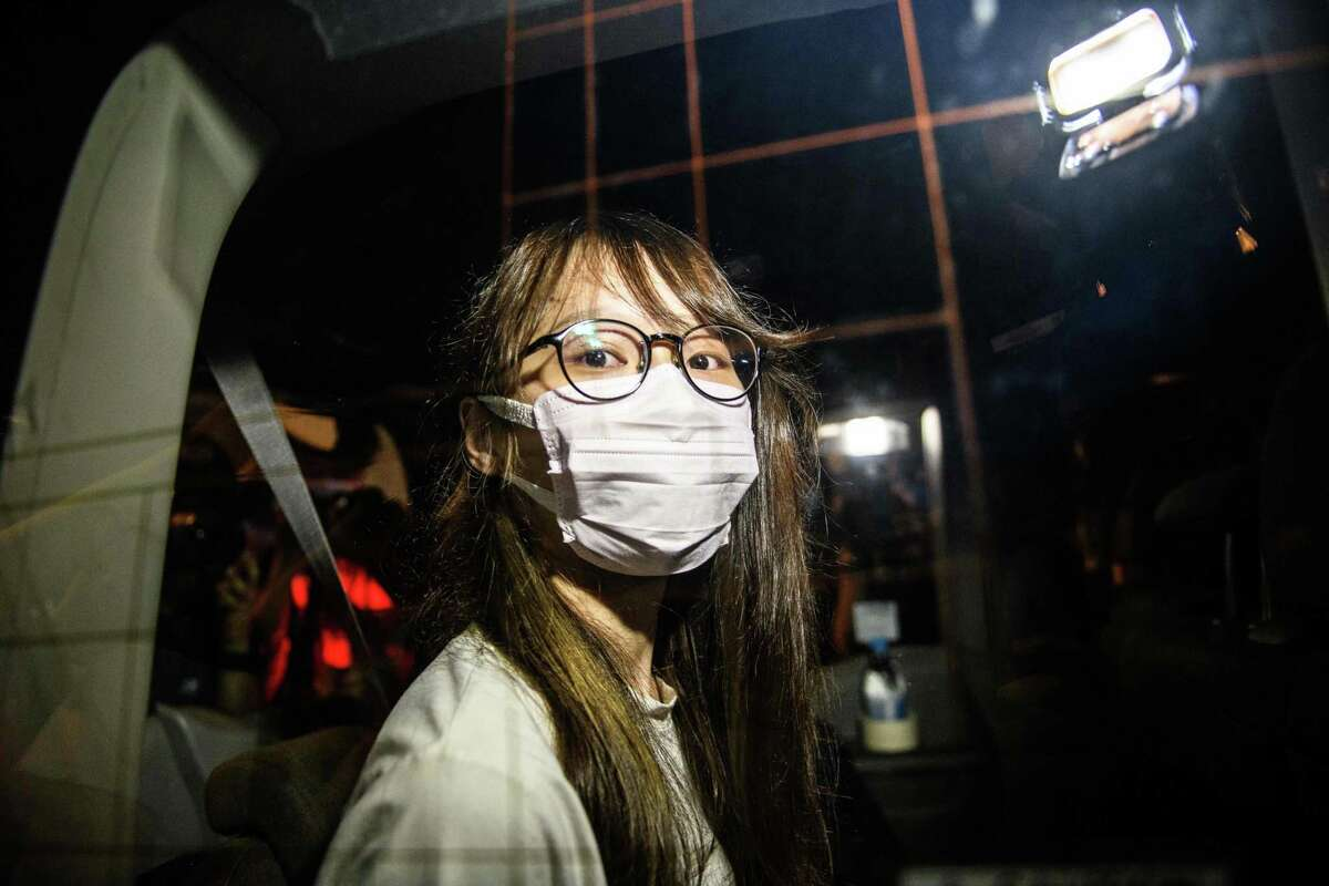 Prominent Hong Kong democracy activist Agnes Chow looks out of a car window while being driven away by police from her home after she was arrested under the new national security law in Hong Kong late on August 10, 2020. - Chow was arrested late on August 10 under China's new national security, a police source and a statement on her verified Facebook account said.