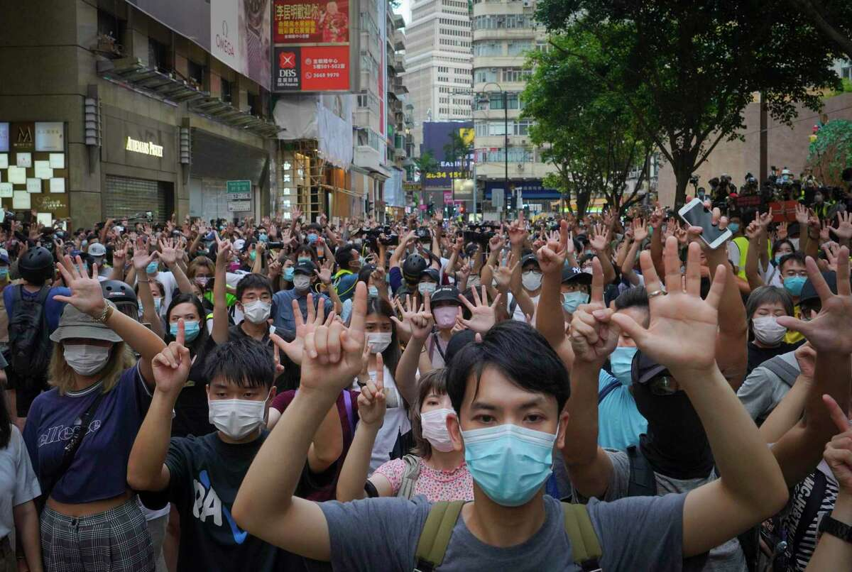 Protesters against the new national security law gesture with five fingers, signifying the