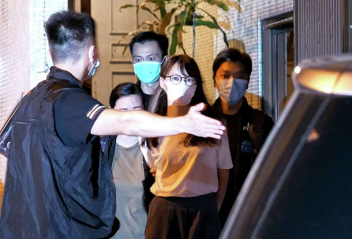 Prominent Hong Kong democracy activist Agnes Chow (C) is lead away by police from her home after she was arrested under the new national security law in Hong Kong late on August 10, 2020. - Chow was arrested late on August 10 under China's new national security, a police source and a statement on her verified Facebook account said.