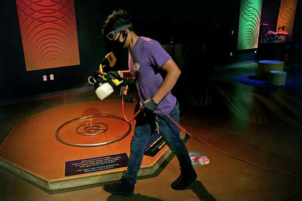 Walter Fica sprays down a display with disinfectant as he and other staff members at the DoSeum perform a thorough burst cleansing of the entire children's museum between blocks of visitors.