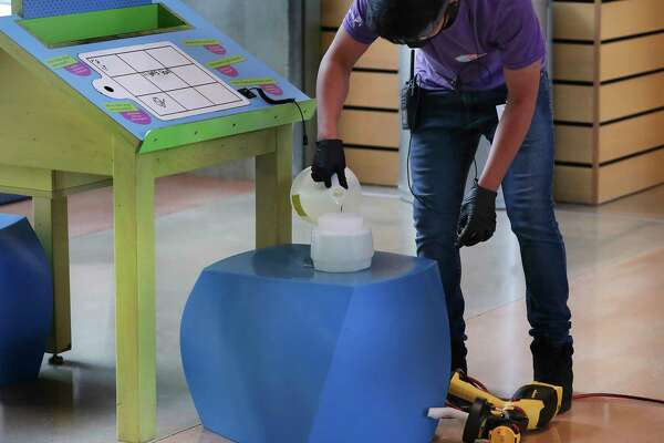 Walter Fica refills a sprayer with disinfectant as he and other staff members at the DoSeum perform a thorough burst cleansing of the entire children's museum between blocks of visitors.