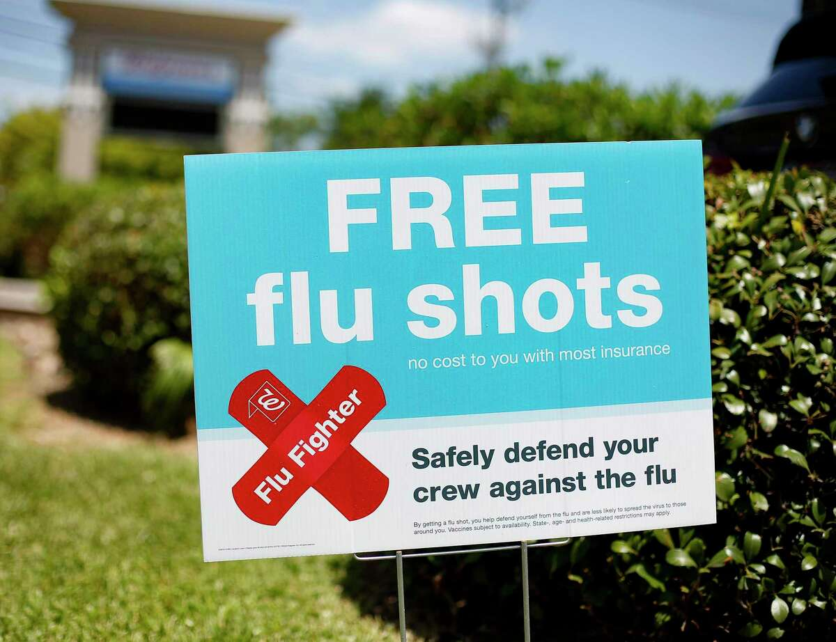 Signs for free flu shots outside the Walgreens in Houston on Thursday, Aug. 13, 2020.