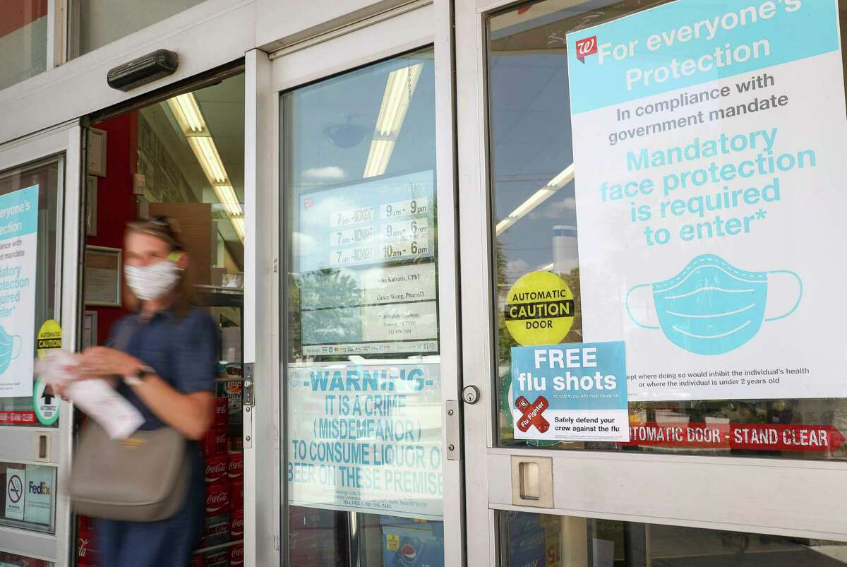 A sign advertises flu shots as a customer leaves after shopping Thursday, Aug. 13, 2020, at a Walgreens location in Houston.