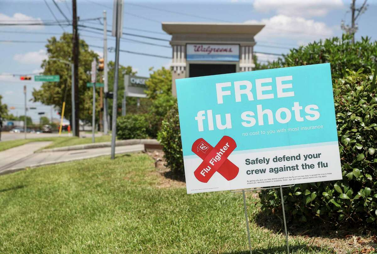 A sign advertises flu shots Thursday, Aug. 13, 2020, at a Walgreens location in Houston.