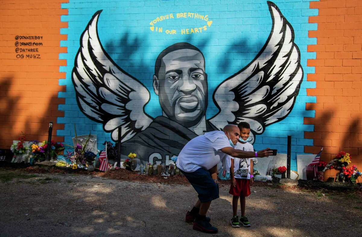 Matthew Mouton, 44, takes a selfie with his son Matthew Mouton Jr., 6, in front of the George Floyd mural in Third Ward on Wednesday, Aug. 12, 2020, in Houston. Mouton took his son to see the mural because he wants his son to start learning about giving back to the community early on in life and also to pay their respects to Floyd.