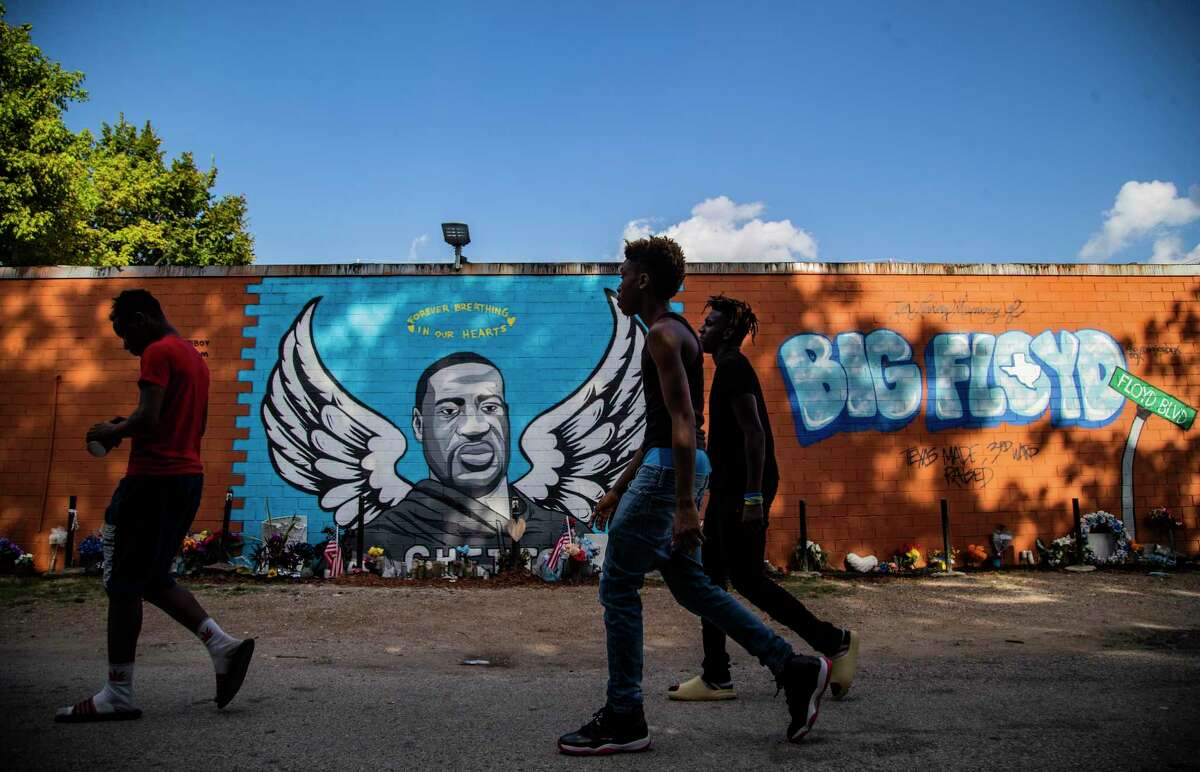 Three young men walk in front of the George Floyd mural in Third Ward on Wednesday, Aug. 12, 2020, in Houston.