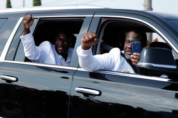 George Floyd's brothers pump their fists to the crowds outside of the Houston Gardens Cemetery, in Pearland, Tuesday, June 8, 2020.