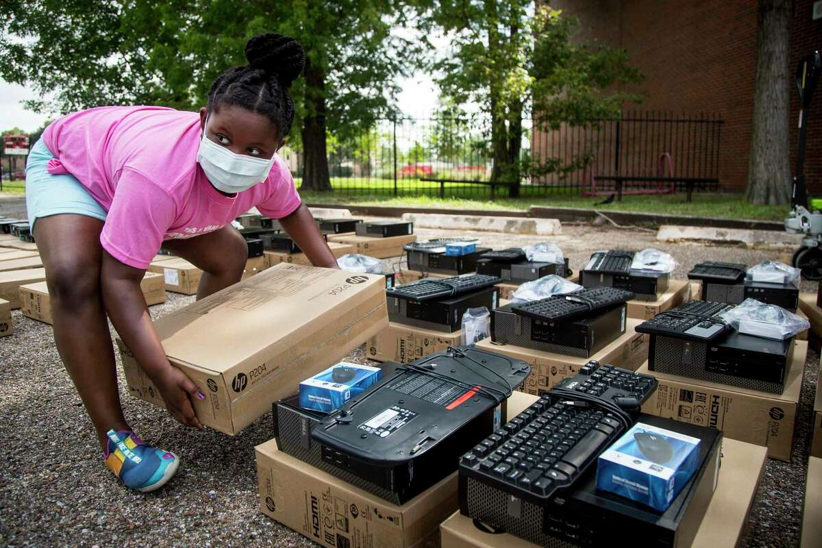 Eight-year-old Sloane Callander, pictured in May, picks up a computer monitor as she helps distribute computers arranged through a partnership between Communities In Schools and Comp-U-Dopt to students at Houston ISD's Hogg Middle School. Tens of thousands of HISD students likely lack access to computers at home, prompting district officials to allocate another $31 million in technology spending this fiscal year.