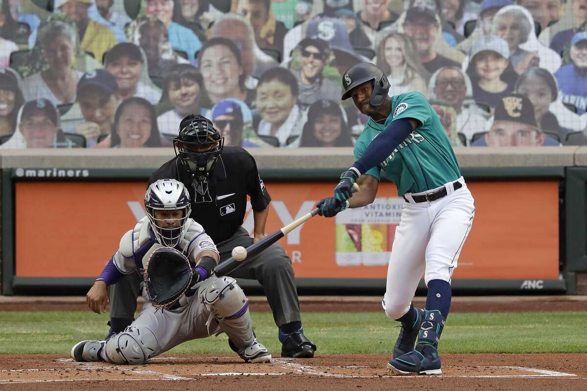 As likenesses of fans look on from the stands, Seattle Mariners' Kyle Lewis, right, lines out as Colorado Rockies catcher Elias Diaz, front left, looks on in the first inning of a baseball game Friday, Aug. 7, 2020, in Seattle. (AP Photo/Elaine Thompson)