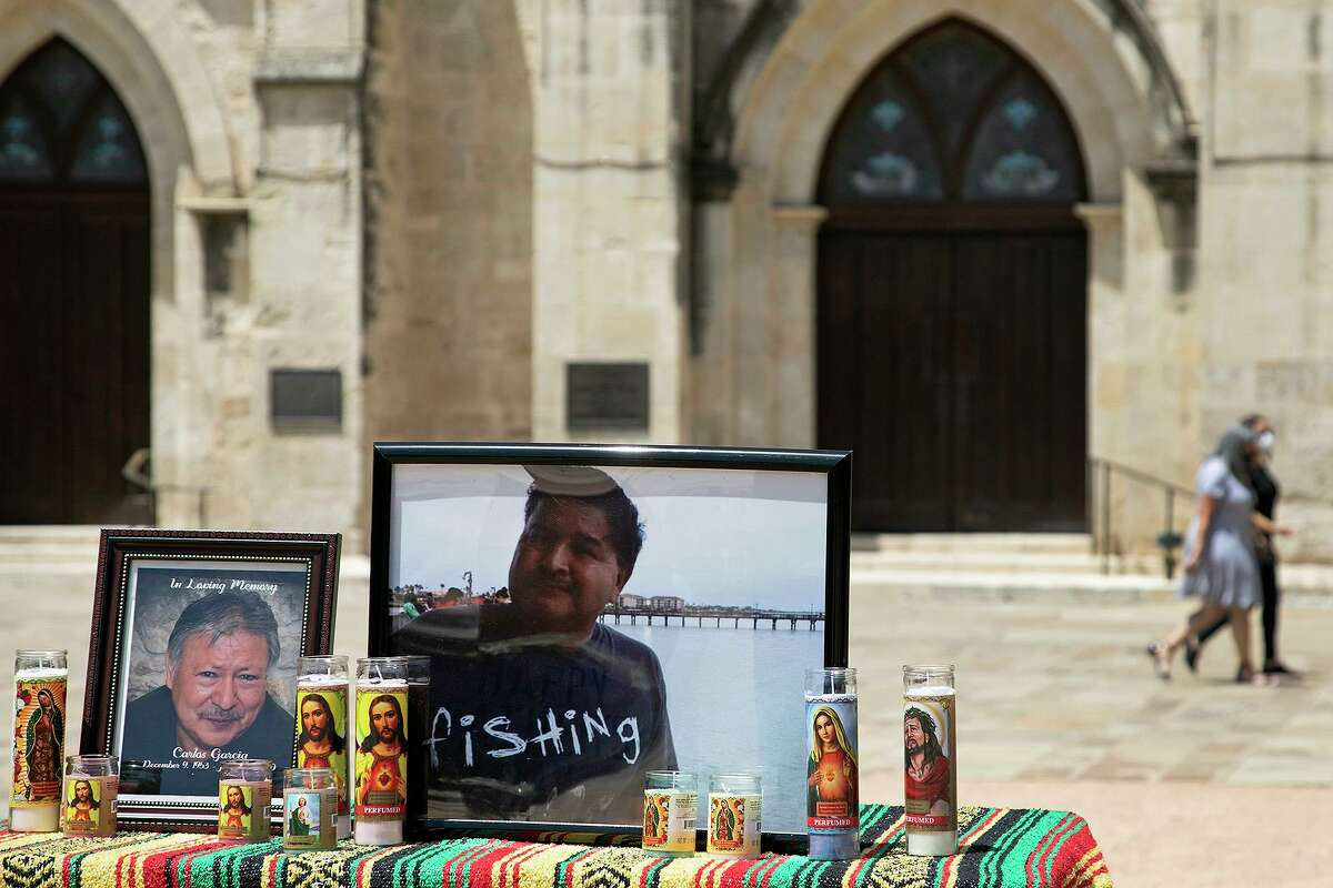 Photos of Carlos Garcia, left, of San Antonio, and Juan Carlos Rangel, of Brownsville, both victims of COVID-19, are featured on the ofrenda set up by their family members for the Marked by Covid vigil, part of the Marked By COVID National Day of Action, in front of San Fernando Cathedral in Main Plaza on Thursday, August 13, 2020.