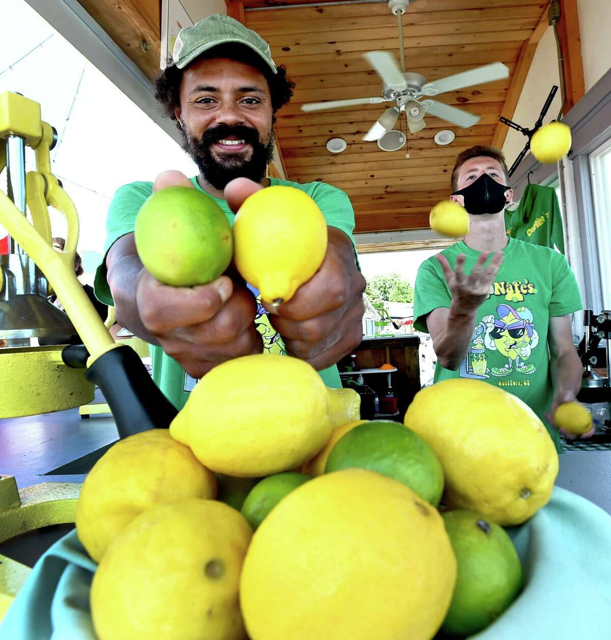 Nate Bryant, owner of LemonNates lemonade and limeade, stands on the dock at the Guilford Mooring restaurant in Guilford, on Thursday, July 16. LemonNate's offers fresh squeezed lemonade and limeade. All drinks are individually made. At right is employee Sean Fitzgerald.