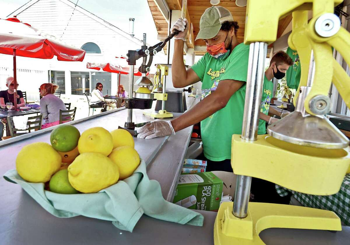 Guilford, Connecticut - Thursday, July 16, 2020: Nate Bryant, owner of LemonNates at the Guilford Mooring in Guilford, left, squeezes a lemon to make lemonade at his lemonade-limeade stand on the dock at the Guilford Mooring in Guilford. All drinks are individually made. A customer can have fresh strawberries, mint, basil and cucumbers added added to their offerings. Employee Sean Fitzgerald prepares a lemonade, right. He shared his secret to making the best fresh squeezed lemonade.