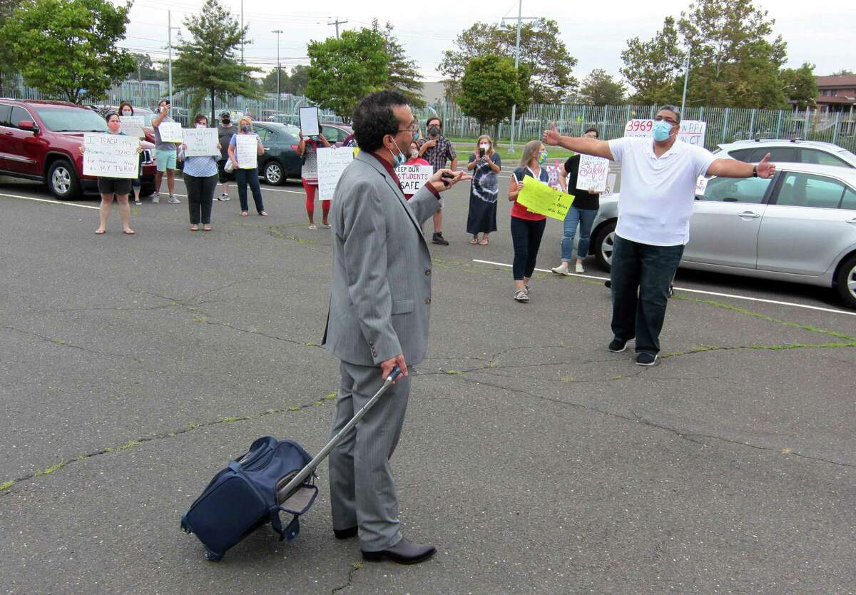 Bridgeport Board of Education member Joseph Sokolovic, center, makes a point as he and teacher Emilio Reales argue about opening schools in the fall during a protest by teachers at the Aquaculture Education Center in Bridgeport, Conn., on Thursday Aug. 13, 2020. Many teachers are worried about COVID-19 spreading as students return to the classrooms.