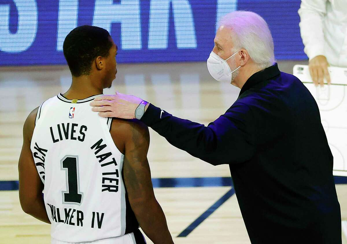 Spurs head coach Gregg Popovich, right, talks with Lonnie Walker IV during the first quarter against the Utah Jazz on Aug. 13, 2020, in Lake Buena Vista, Fla.