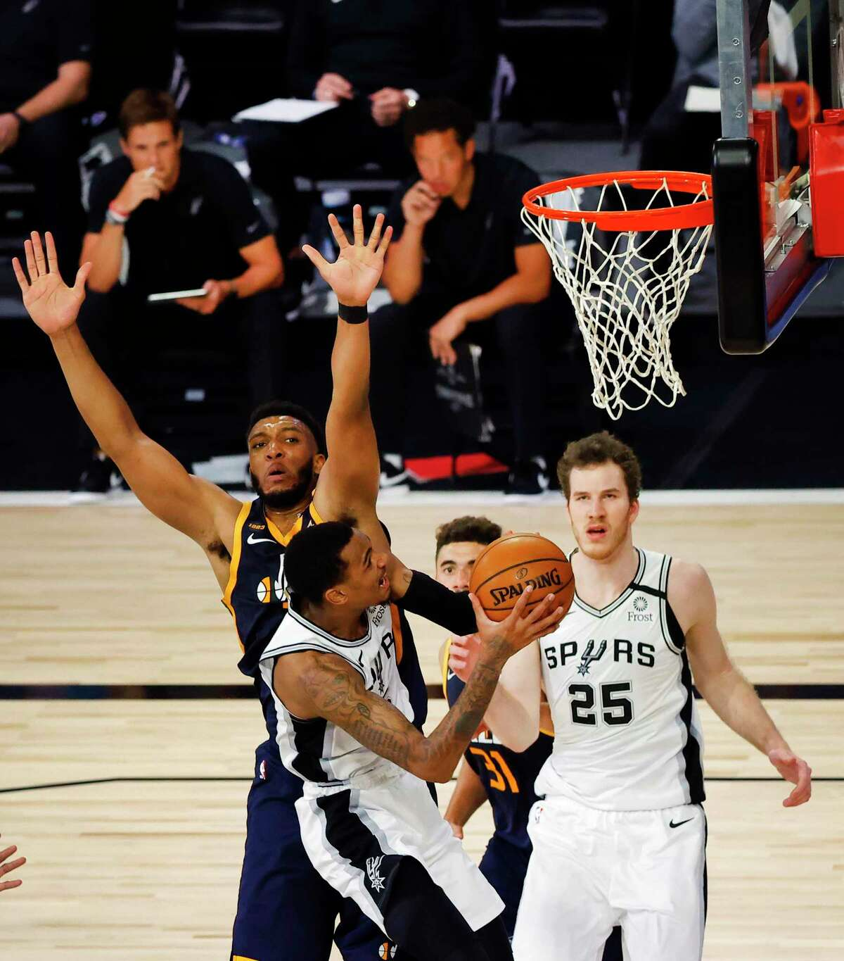 The Spurs' Dejounte Murray scores two of his 12 points against the Jazz's Tony Bradley on Thursday. At 32-29, it was the Spurs' first losing season since 1996-97.
