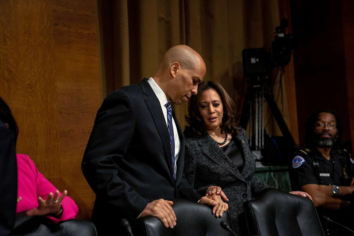 FILE - Sens. Cory Booker (D-N.J.) and Kamala Harris (D-Calif.) confer during the Senate confirmation hearing for Supreme Court nominee Brett Kavanaugh in Washington on Sept. 27, 2018. President Donald Trump took aim at Harris after former Vice President Joe Biden, the presumptive Democratic presidential nominee, chose her as his running mate. (Erin Schaff/The New York Times)