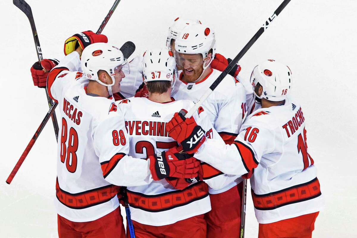 Carolina Hurricanes' Dougie Hamilton (19) celebrates his goal against the Boston Bruins with teammates Martin Necas (88), Andrei Svechnikov (37) and Vincent Trocheck (16) during the third period of an NHL Eastern Conference Stanley Cup hockey playoff game in Toronto, Thursday, Aug. 13, 2020. (Chris Young/The Canadian Press via AP)