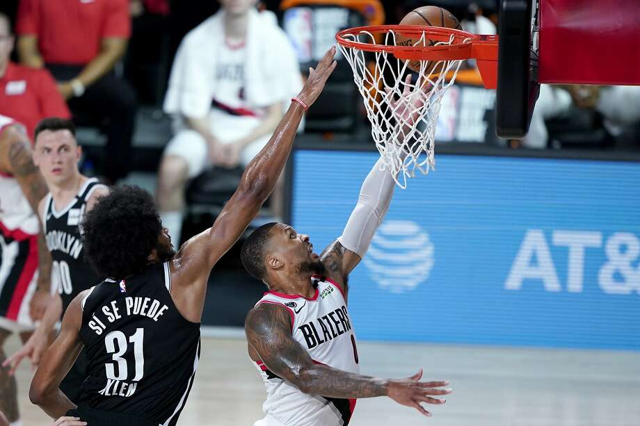 Portland Trail Blazers' Damian Lillard, right, goes up for a shot against Brooklyn Nets' Jarrett Allen (31) during the first half of an NBA basketball game Thursday, Aug. 13, 2020 in Lake Buena Vista, Fla. (AP Photo/Ashley Landis, Pool) Photo: Ashley Landis / Associated Press