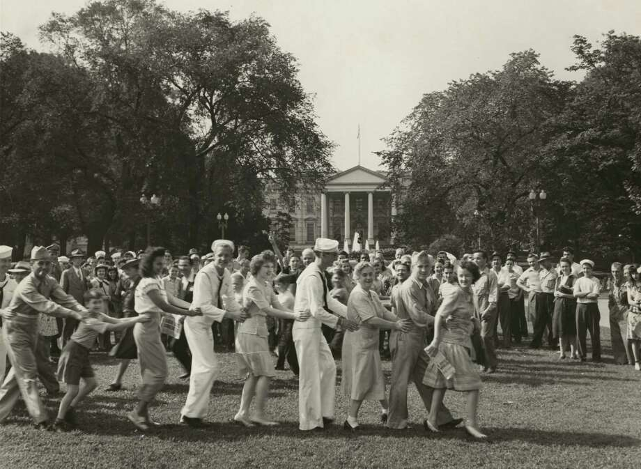 In this 1945 photo, a jubilant crowd dances on the White House lawn on V-J Day following Japan's surrender. Photo: Library Of Congress. / Library of Congress
