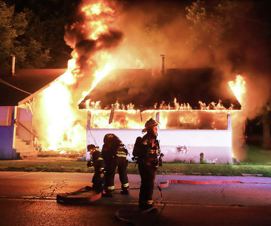 "Alton firefighters set up to battle a raging fire in a duplex early Friday morning at 1201 E. 7th Street in Alton. The fire spread to another duplex, left, at 1203 E. 7th Street. East Alton firefighters were called to the scene for mutual aid. Three ""kids"" were decribed as having escaped the apartment on the far right before firefighters arrived. No injuries were reported."