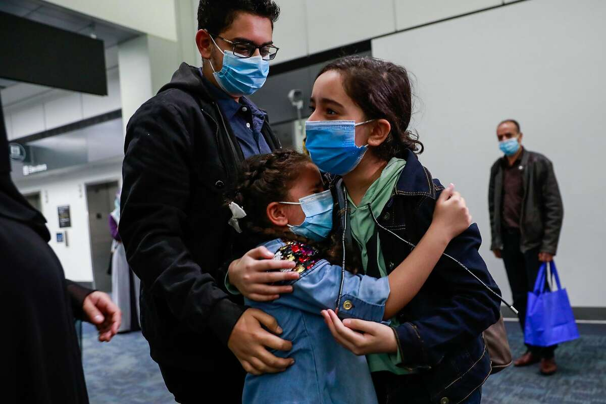 Raghad Saleh,10, (right) embraces her sister Maya Saleh,8, (center) and brother Ahmed Saleh,14, after arriving from her journey from Egypt after being separated from their family due to a visa issue at San Francisco International airport on Thursday, Aug. 13, 2020 in San Francisco, California. Raghad Saleh, was stranded in Egypt without her family after the Trump administration refused to give her a visa, despite granting one to her parents and three siblings. The family, who waited years for the visas, settled in the Bay Area in early July.