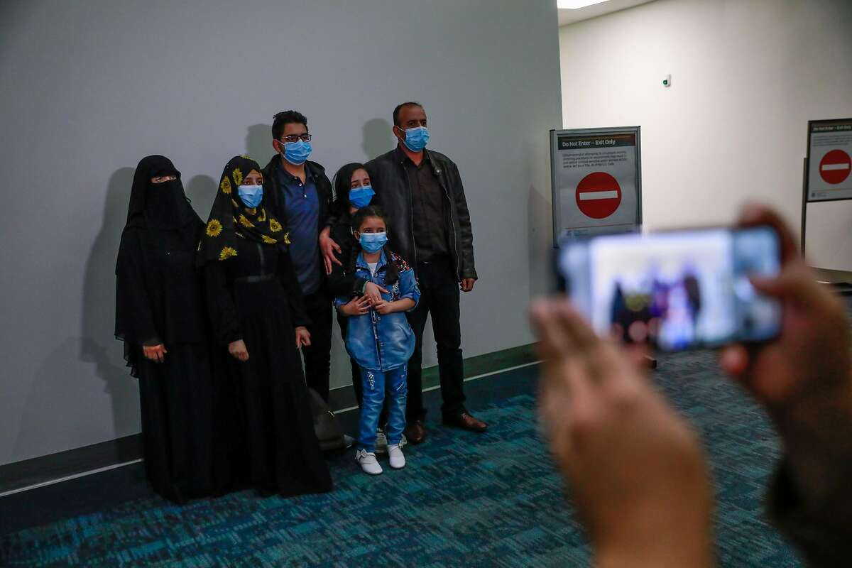 The Saleh family poses for a photo moments after Raghad Saleh, 10 (second from right) arrived from Egypt after being separated from their family due to a visa issue at San Francisco International airport on Thursday, Aug. 13, 2020 in San Francisco, California. Raghad Saleh, was stranded in Egypt without her family after the Trump administration refused to give her a visa, despite granting one to her parents and three siblings. The family, who waited years for the visas, settled in the Bay Area in early July.