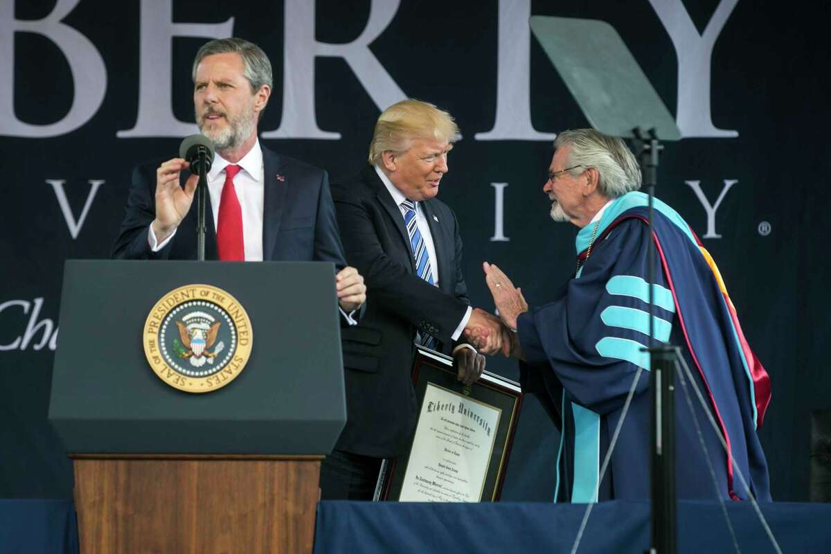From left: Liberty University president Jerry Falwell speaks as President Donald Trump receives an honorary degree from Provost Ronald Hawkins at the commencement address for LIberty University's class of 2017, in Lynchburg, Va., May 13, 2017. Falwell, one of Trump's most prominent and controversial evangelical supporters, will take an indefinite leave of absence from his role as president and chancellor of Liberty University, the board of trustees announced in August 2020.
