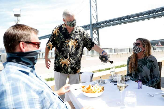 Managing partner Pete Sittnick (center) pours champagne for Todd Caine and Karen Dexter at Waterbar in San Francisco, Calif., on Thursday, August 13, 2020. San Francisco's power lunch scene has become relaxed during pandemic.