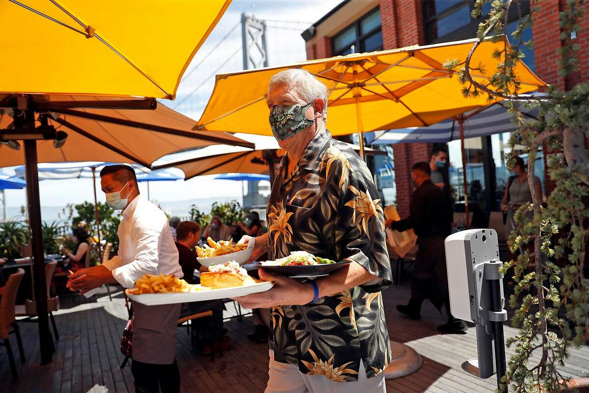 Managing partner Pete Sittnick delivers lunch at Waterbar in San Francisco, Calif., on Thursday, August 13, 2020. San Francisco's power lunch scene has become relaxed during pandemic.