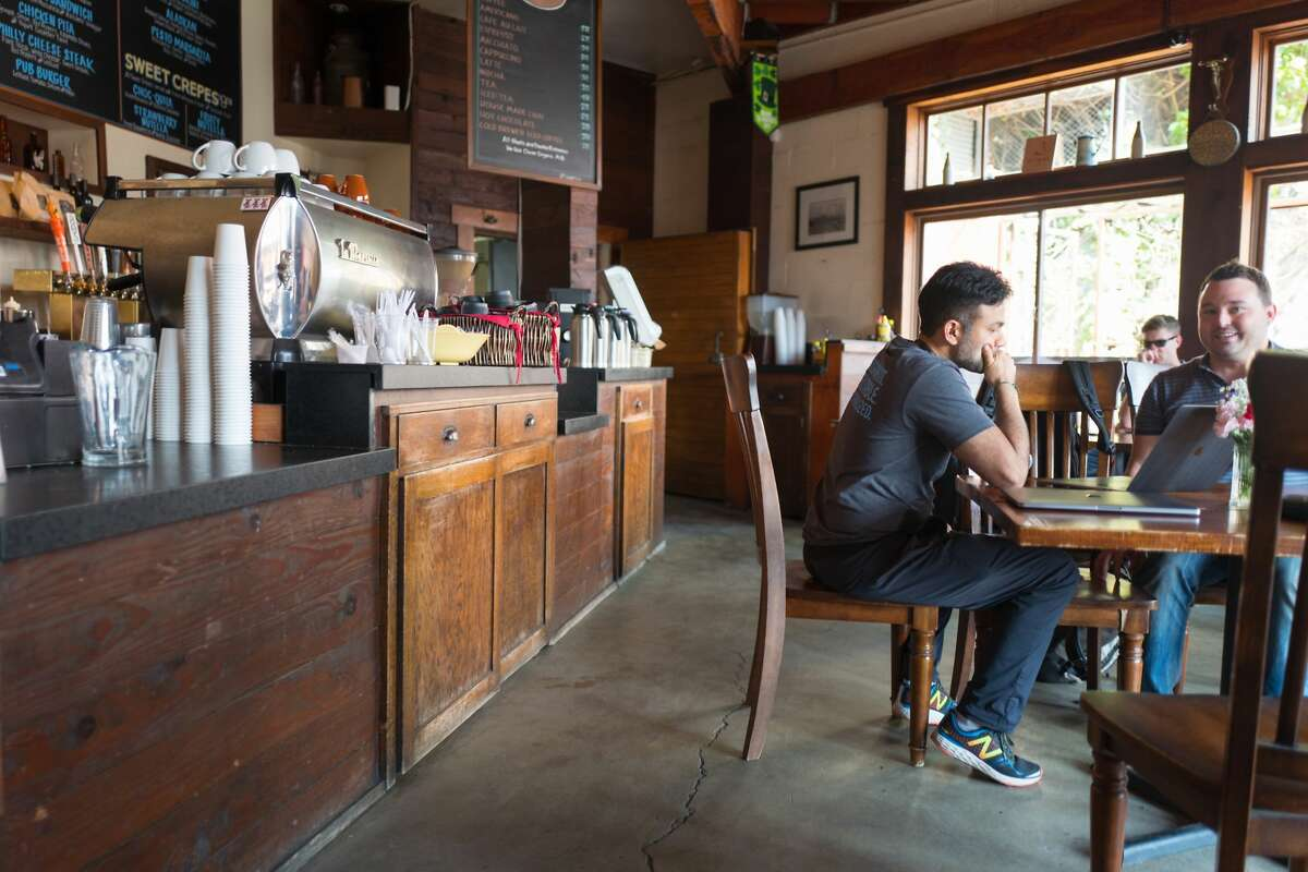 Two men sit at a table during a meeting, one with a laptop, at the Creamery, a restaurant popular with technology startup members and venture capitalist investors in the South of Market (SoMa) neighborhood of San Francisco, California, October 13, 2017. (Photo by Smith Collection/Gado/Getty Images)