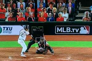 Cutouts representing the late President George H.W. Bush and First Lady Barbara Bush  appear behind home plate at a Minute Maid Park during the short, fan-less 2020 season.
