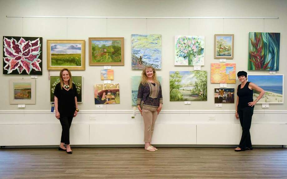 ASOG co-President Elaine Conner, left, ASOG board member and exhibit co-chair Reese Anderson Green, center, and ASOG co-President Julie DiBiase pose among work displayed in the Art Society of Old Greenwich Summer Pop-Up Exhibit at the Greenwich Botanical Center in the Cos Cob section of Greenwich, Conn. Thursday, Aug. 13, 2020. 63 pieces from 37 local artists are on display and for sale in the show, which was judged by Parsons School of Design art history professor Barbara M. Laux, Ph.D. The reception, featuring live music by Chris Fiore, will be held with mandatory masks and social distancing on Saturday, Aug. 15 at 3 p.m. Photo: Tyler Sizemore / Hearst Connecticut Media / Greenwich Time