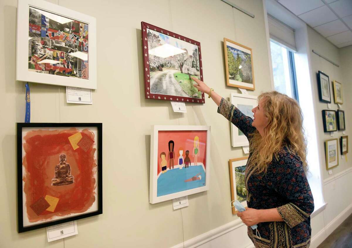 ASOG board member and exhibit co-chair Reese Anderson Green points out mixed media pieces displayed in the Art Society of Old Greenwich Summer Pop-Up Exhibit at the Greenwich Botanical Center in the Cos Cob section of Greenwich, Conn. Thursday, Aug. 13, 2020. 63 pieces from 37 local artists are on display and for sale in the show, which was judged by Parsons School of Design art history professor Barbara M. Laux, Ph.D. The reception, featuring live music by Chris Fiore, will be held with mandatory masks and social distancing on Saturday, Aug. 15 at 3 p.m.