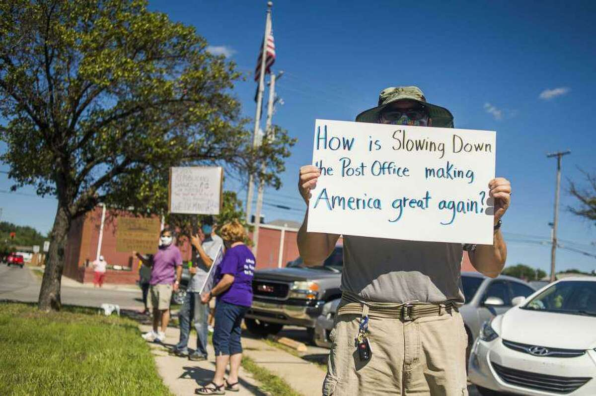 Eric Severson holds a sign as a few dozen people gather in front of the United States Post Office in Midland, Mich., to protest recent changes to the U.S. Postal Service under new Postmaster General Louis DeJoy Tuesday, Aug. 11, 2020 in Midland, Mich.